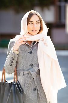 Schöne frau in einem mantel, der auf der straße aufwirft