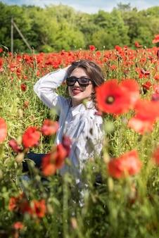 Schöne frau in einem mohnfeld, genießen sie sommerzeit. romantische stimmung naturliebhaber