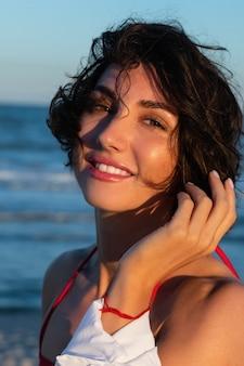 Schöne frau in einem roten badeanzug mit einem lächeln im gesicht glättet ihr haar vor dem hintergrund des meeres. mädchen in einem roten badeanzug vor dem hintergrund des meeres.