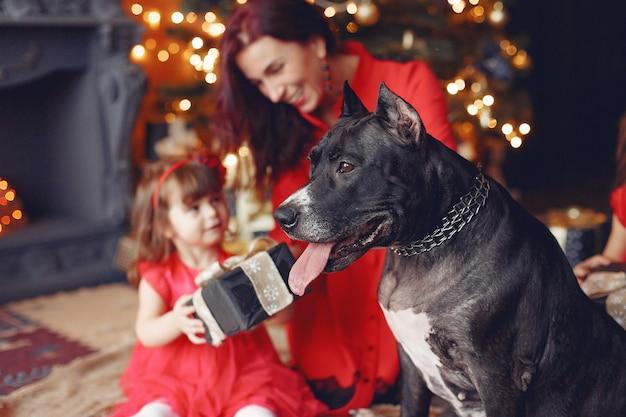Schöne frau in einem roten kleid. familie zu hause. mutter mit tochter. menschen mit einem hund.