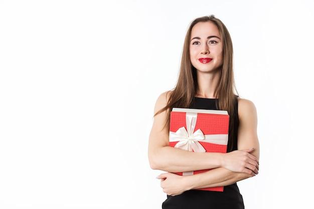 Schöne frau in einem roten kleid mit einem geschenk auf einem weißen hintergrund. überraschung für den urlaub.