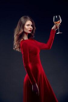 Schöne frau in einem roten kleid mit einem weinglas