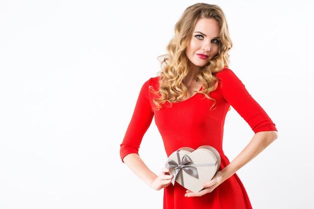 Schöne frau in einem roten kleid mit einer geschenkbox in der form eines herzens. isoliert.