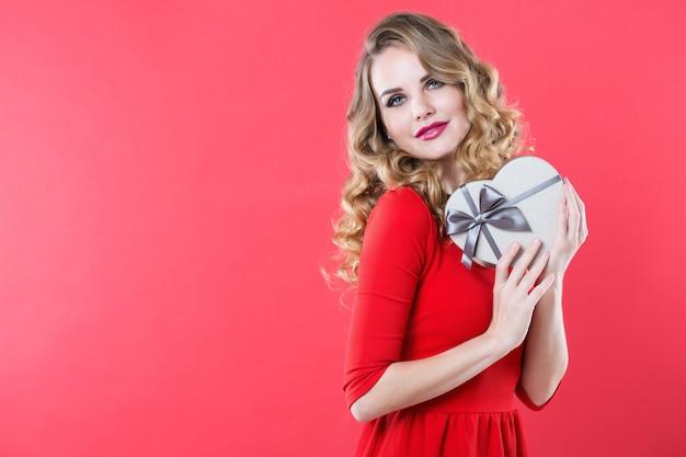 Schöne frau in einem roten kleid mit einer geschenkbox in der form eines herzens
