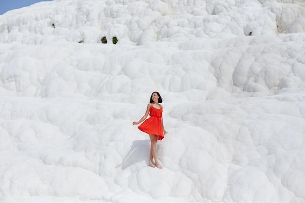 Schöne frau in einem roten kleid steht gegen die weißen berge.