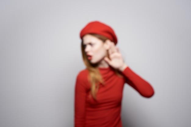 Schöne frau in einem roten pullover kosmetik emotion heller hintergrund