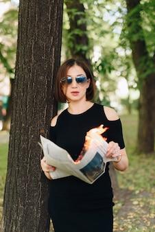 Schöne frau in einem schwarzen kleid in einem park mit einer brennenden zeitung in ihren händen