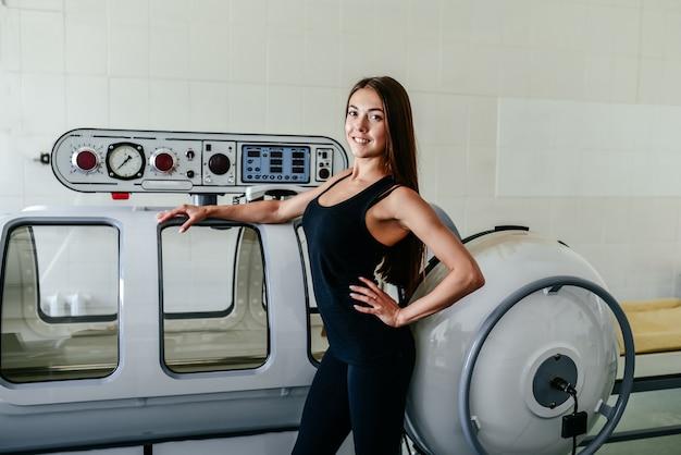 Schöne frau in einem schwarzen t-shirt und einer weißen hose liegt in einer überdruckkammer