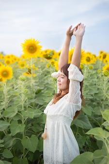 Schöne frau in einem weißen kleid auf einem feld von sommersonnenblumen