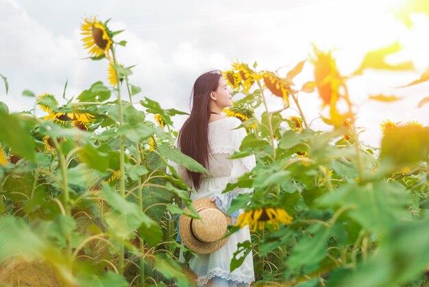 Schöne frau in einem weißen kleid im sonnenblumenfeld