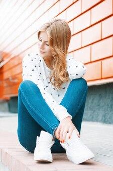 Schöne frau in einem weißen pullover jeans und weißen turnschuhen sitzen auf einer fliese