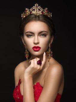 Schöne frau in einer goldenen krone und ohrringen
