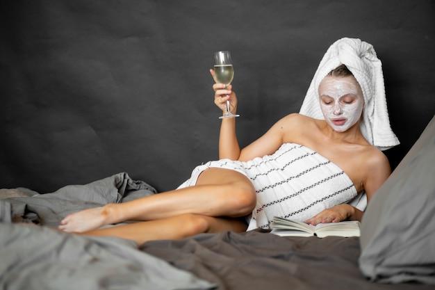 Schöne frau in einer kosmetischen maske und einem handtuch hält ein glas champagner, liest ein buch im bett und lächelt