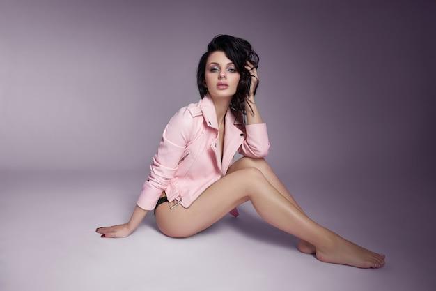 Schöne frau in einer rosa lederjacke mit langen haaren auf dem boden. sexy brünette mädchen