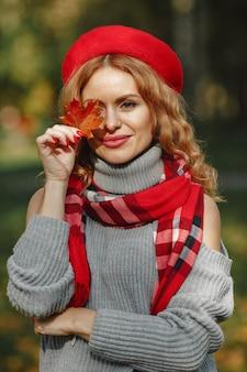 Schöne frau in einer roten baskenmütze halten herbstliches blatt in der hand.