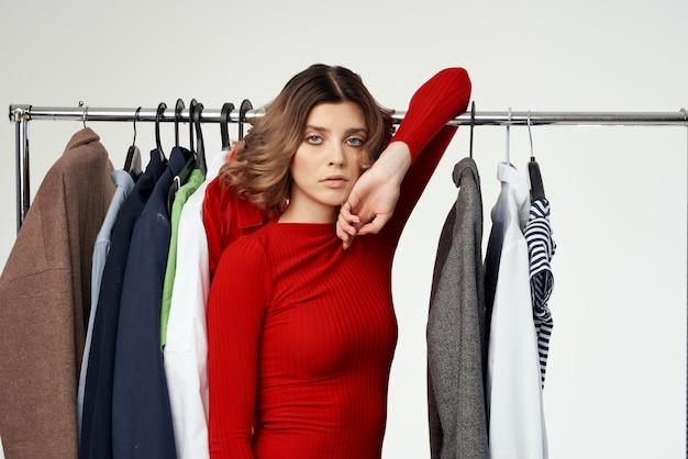 Schöne frau in einer roten jacke in der nähe der garderobe isolierter hintergrund