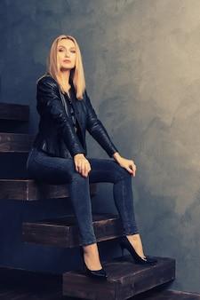 Schöne frau in einer schwarzen lederjacke und in jeans, die auf einer hölzernen auslegerleiter sitzen sitzen. persönliches wachstumskonzept