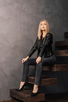 Schöne frau in einer schwarzen lederjacke und in jeans, die auf einer hölzernen auslegerleiter sitzen sitzen