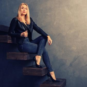 Schöne frau in einer schwarzen lederjacke und jeans, absätze sitzen auf einer hölzernen auslegerleiter. persönliches wachstumskonzept