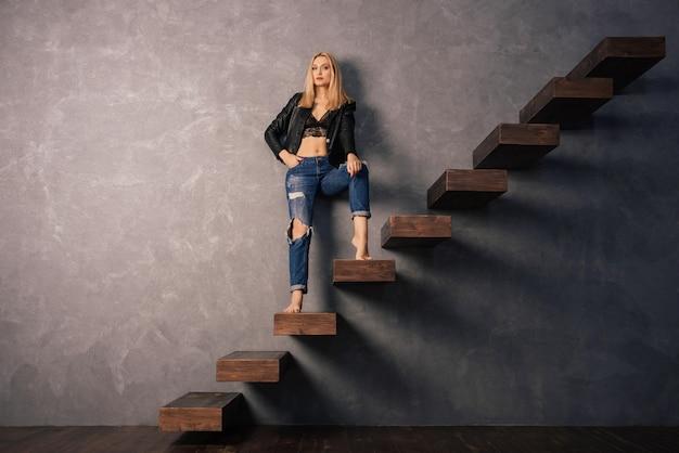 Schöne frau in einer schwarzen lederjacke und zerrissenen jeans, die auf einer hölzernen freitragenden treppe stehen
