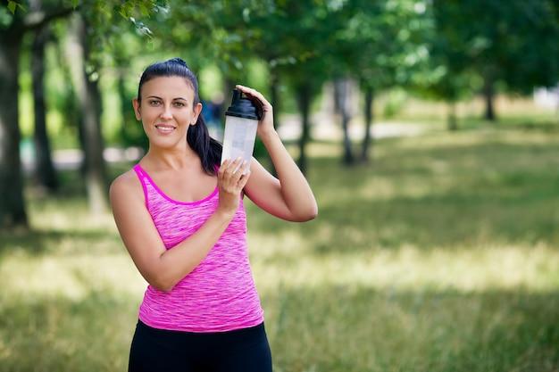 Schöne frau in einer sportuniform hält wasser in ihren händen in einem park