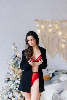 Schöne frau in einer wäsche nahe weihnachtstanne im dekorierten studio