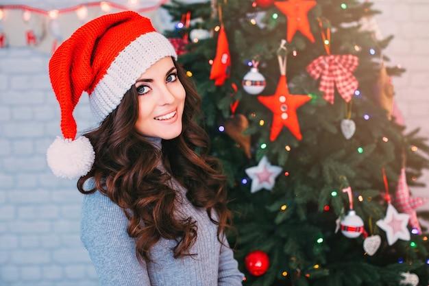 Schöne frau in einer weihnachtsmütze auf weihnachtsbaum. neujahr und weihnachten feiern.