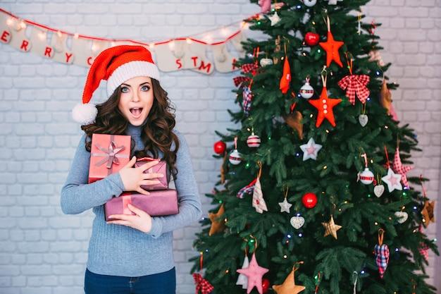 Schöne frau in einer weihnachtsmütze mit vielen geschenkboxen auf weihnachtsbaum. neujahr und weihnachten feiern.