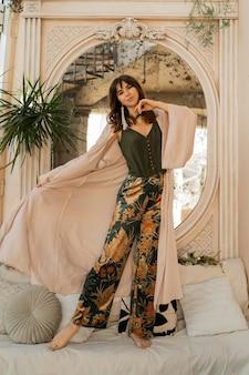 Schöne frau in eleganter frauenkleidung, die im stilvollen böhmischen interieur aufwirft.