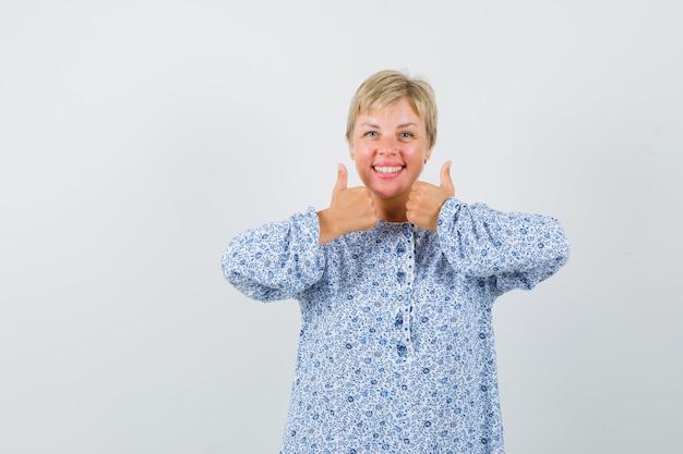 Schöne frau in gemusterter bluse, die daumen oben zeigt, während sie lächelt und lustig schaut, vorderansicht.