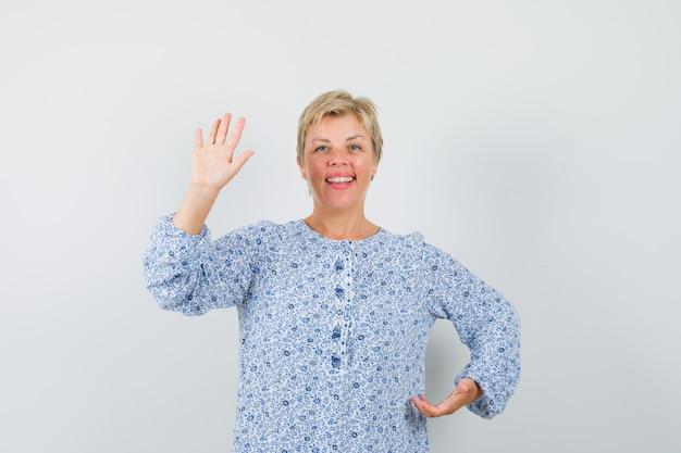Schöne frau in gemusterter bluse, die hand winkt, um sich zu verabschieden und froh zu sehen, vorderansicht.