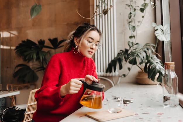 Schöne frau in gläsern und großen ohrringen gießt tee in tasse
