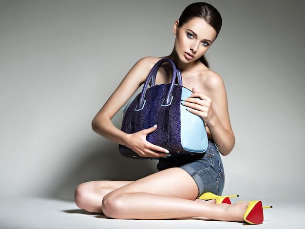 Schöne frau in high heels hält handtasche. mode junges mädchen mit langen beinen, nackter körper, der im studio aufwirft