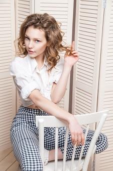 Schöne frau in hose und hemd sitzt auf einem stuhl vor einer jalousie
