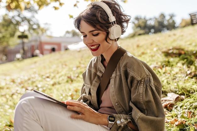 Schöne frau in jacke und kopfhörern, die draußen auf gras sitzen. glückliche frau mit lockiger frisur, die smartphone draußen hält.