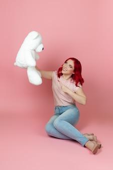 Schöne frau in jeans mit roten haaren hält einen großen weißen teddybär auf dem boden sitzend