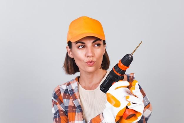 Schöne frau in kariertem hemd, hut und handschuhen, an grauer wand hält bohrer, um selbstbewusstes glückliches lächeln zu reparieren