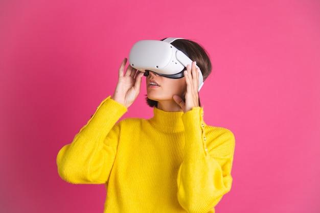 Schöne frau in leuchtend gelbem pullover auf rosa in virtual-reality-brille glücklich aufgeregt überglücklich berühren luft