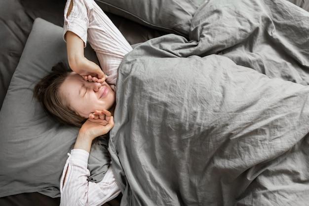 Schöne frau in nachtwäsche streckt sich zu hause im bett und lächelt aus einer guten pause. gesunder schlaf. draufsicht