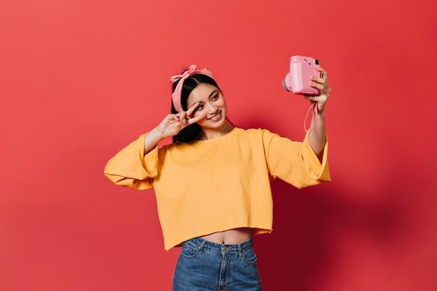 Schöne frau in orangefarbenem pullover und jeans zeigt friedenszeichen und macht selfie