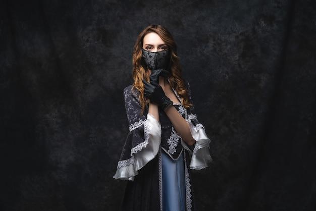 Schöne frau in renaissance-kleid, gesichtsmaske und handschuhen, coronavirus, covid-19-schutzkonzept.