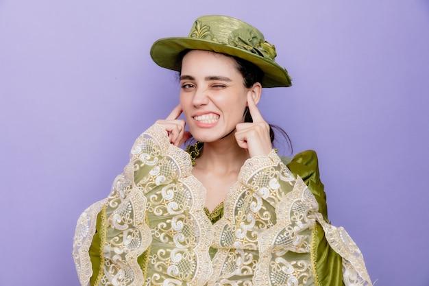 Schöne frau in renaissance-kleid und hut, die ohren mit verärgertem ausdruck schließt, der auf blau gereizt ist