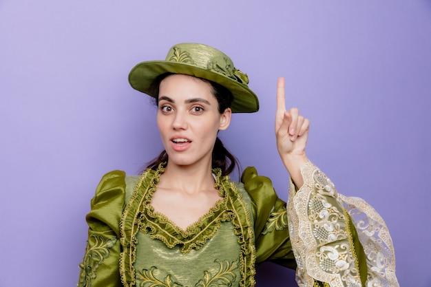 Schöne frau in renaissance-kleid und hut mit einem lächeln auf einem intelligenten gesicht, das mit dem zeigefinger nach oben zeigt und eine neue idee auf blau hat