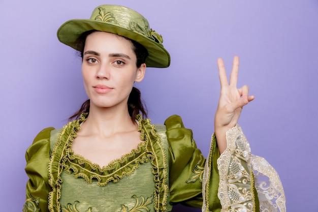 Schöne frau in renaissance-kleid und hut mit selbstbewusstem lächeln im gesicht, die nummer zwei auf blau zeigt