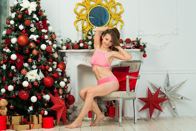 Schöne frau in rosa dessous in der nähe von weihnachtstanne in dekoriertem studio