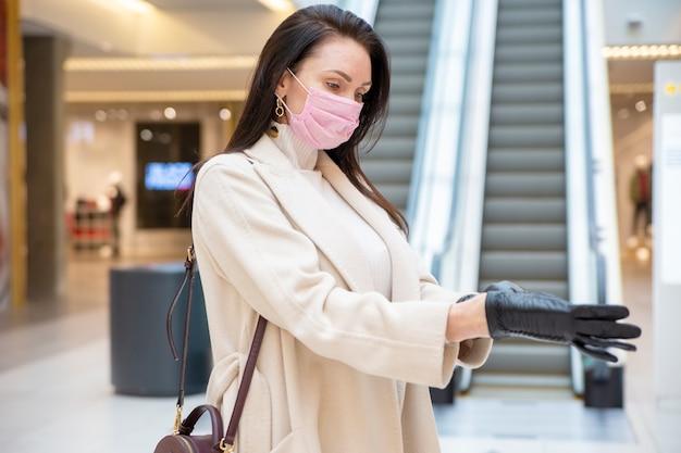 Schöne frau in rosa medizinischer maske, die an einem öffentlichen ort auf einer rolltreppe im hintergrund lederhandschuhe anzieht