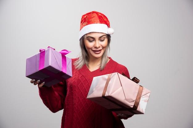 Schöne frau in santa hut, die glücklich weihnachtsgeschenke betrachtet.