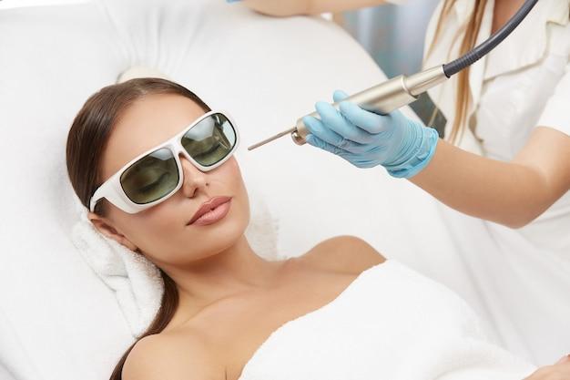 Schöne frau in schutzbrille am kosmetikzentrum, das haarentfernung für ihre wange durch professionelle kosmetikerin erhält