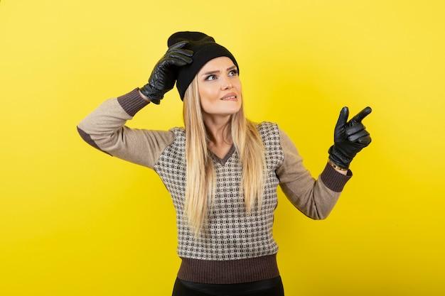 Schöne frau in schwarzen handschuhen und hut, die auf gelb stehen.