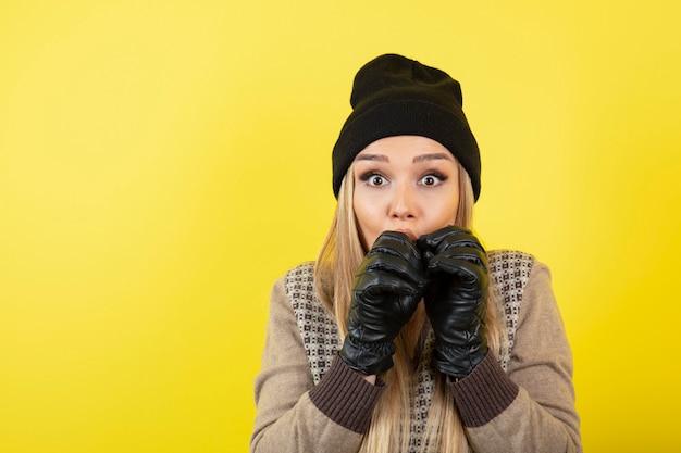 Schöne frau in schwarzen handschuhen und hut, die sich kalt anfühlt.